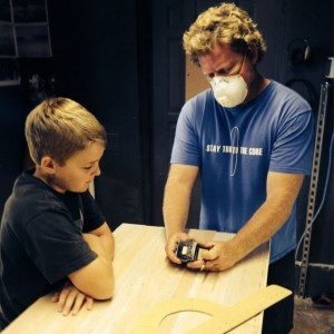 Josh Martin in the shaping bay with a local grom.