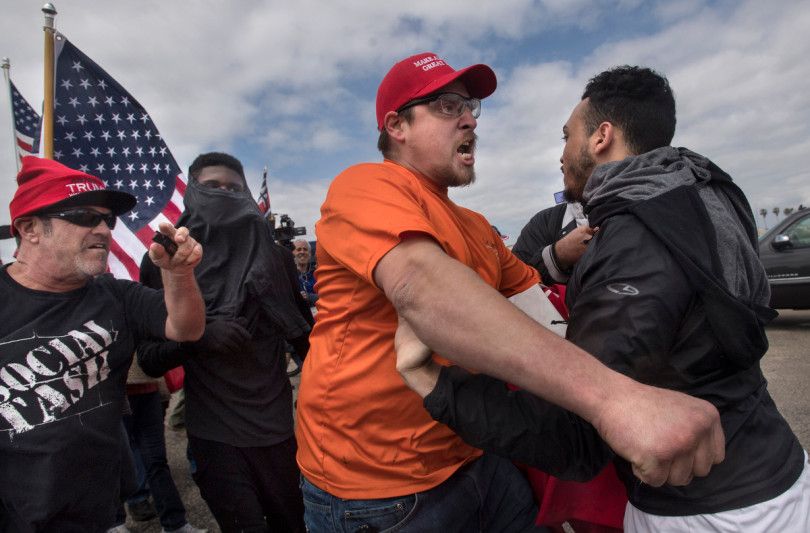 A pro-Trump marcher, center, and an anti-Trump protester clash as the two sides come together in Huntington Beach, CA on Saturday, March 25, 2017. (Photo by Mindy Schauer, Orange County Register/SCNG)