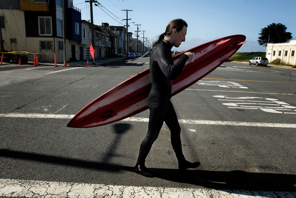 "Mark ""Doc"" Renneker drinks a cup of coffee as he walks to Ocean Beach in San Francisco, CA, on May 25, 2006. Renneker, a renowned big wave surfer, was one of the first to ride at the famous break known as Mavericks."